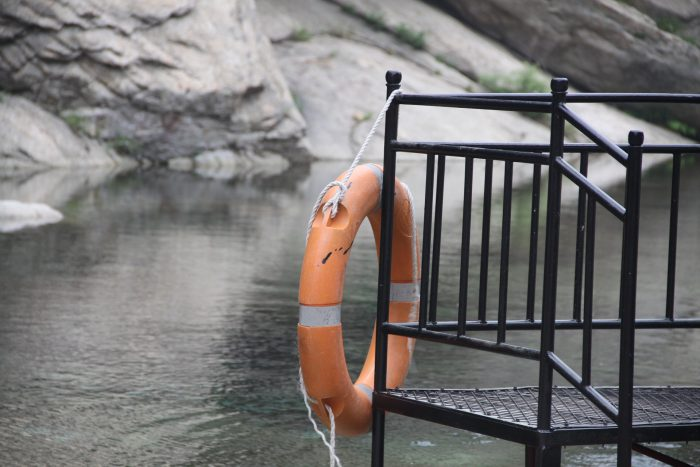 lake with a orange life preserver hanging on a metal railing.