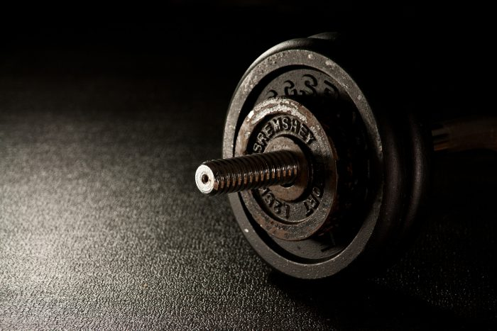 a black rubber surface with the end of a metal dumbbell layed on top of it.