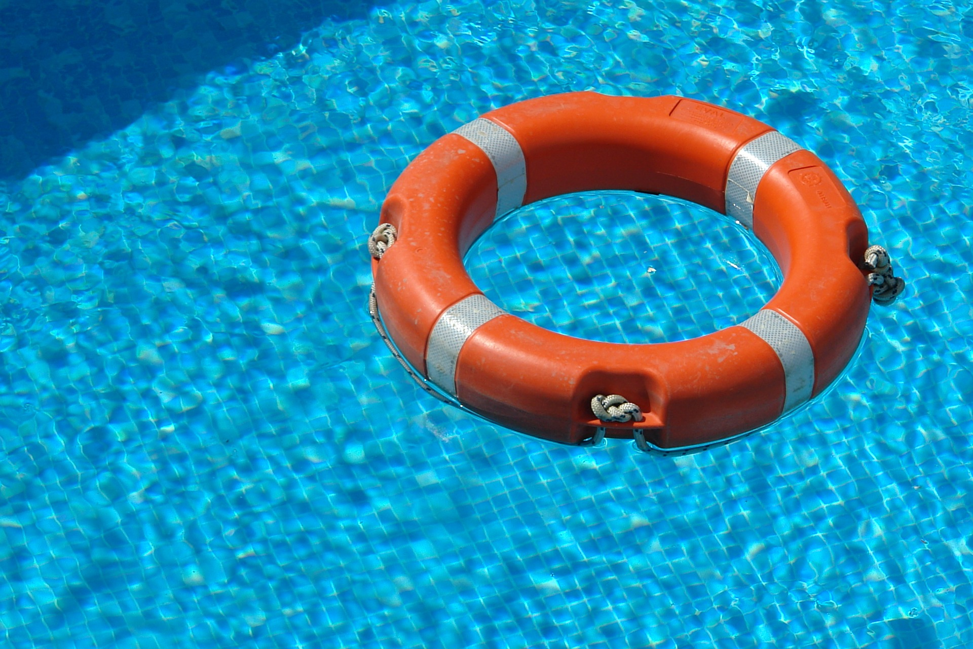 swimming pool water with an orange floating safety device